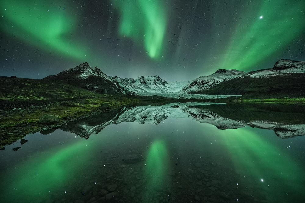 欧若拉被映照在冰岛冬季寒冷的湖面上